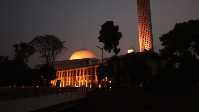WS tilt down from illuminated minaret to spherical dome of Istiqlal Mosque at dusk WS low angle view of minaret and spherical dome of Istiqlal Mosque...