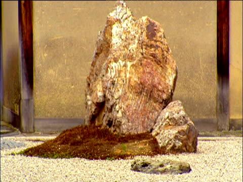 tilt down from large rocks to gravel in ryoanji zen rock garden kyoto - chan buddhism stock videos & royalty-free footage
