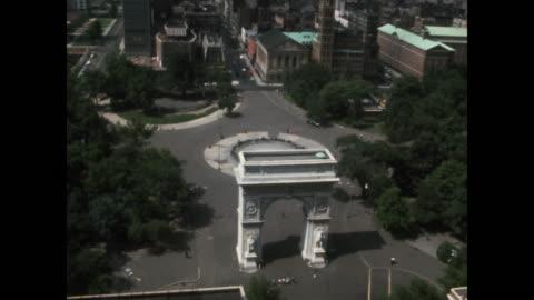 vidéos et rushes de tilt down from lower manhattan skyline in the 1960s to the washington square arch in washington square park in new york city. - segment monté