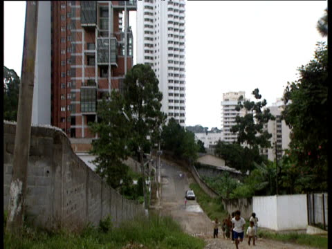 tilt down from modern high rise apartments and pan left to children running through shanty town sao paulo - 社会問題点の映像素材/bロール