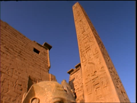 tilt down from obelisk to close up of statue of Ramses in Luxor Temple ruins / Luxor, Egypt