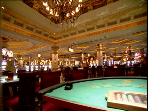 vídeos de stock, filmes e b-roll de tilt down from ornate ceiling and pan right across empty card tables in casino - estilo dos anos 2000