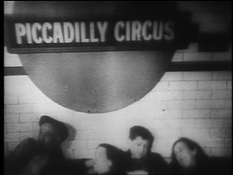 vidéos et rushes de b/w 1940 tilt down from piccadilly circus subway sign to family lying on floor of station / london blitz - 1940