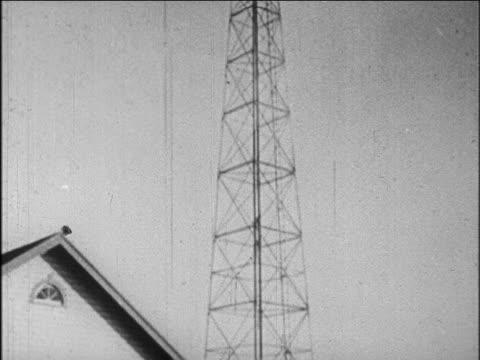 b/w 1927 tilt down from radio tower to house / newsreel - 1927年点の映像素材/bロール