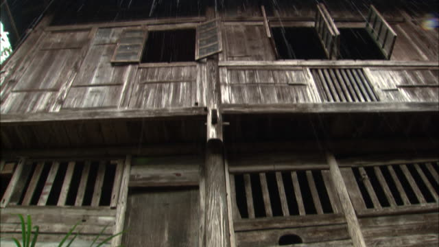 tilt down from rain falling between eaves of wooden houses to water pouring down gutter in ping'an village, guilin, guangxi zhuang - eaves stock videos and b-roll footage