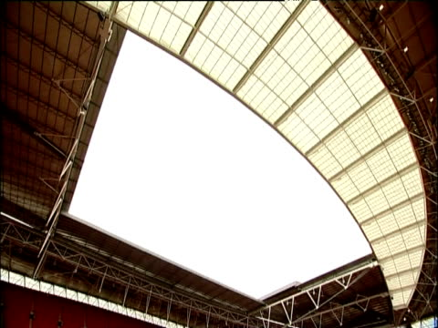 tilt down from roof to pitch and rows of seats inside wembley stadium london - wembley stadium stock videos & royalty-free footage