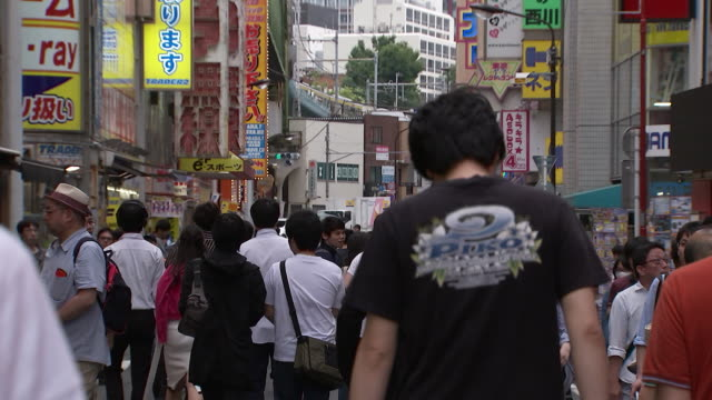 tilt down from signs to show people walking on a street in tokyo, japan. - (war or terrorism or election or government or illness or news event or speech or politics or politician or conflict or military or extreme weather or business or economy) and not usa点の映像素材/bロール