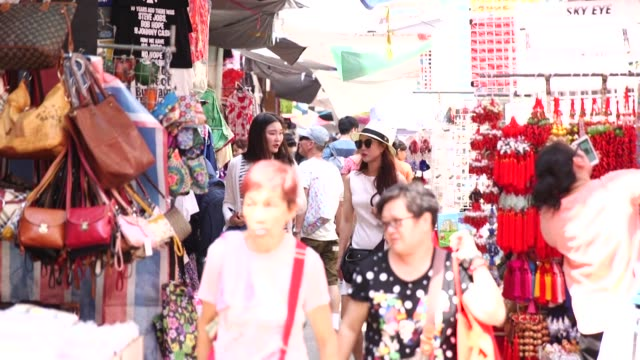 tilt down from sky and top of buildings to the ladies street market entrance in the mong kok district of hong kong china on monday sept 12 shppers... - mong kok stock videos and b-roll footage