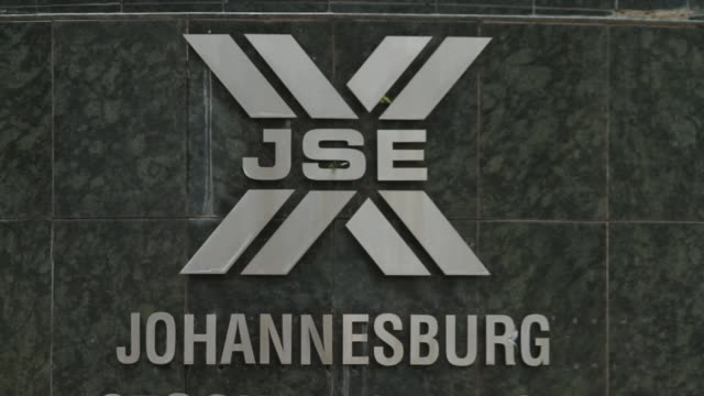 stockvideo's en b-roll-footage met tilt down from south african national flag to entrance to the johannesburg stock exchange in the sandton district of johannesburg south africa on... - gauteng provincie