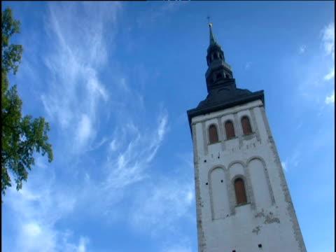 Tilt down from St Nicholas church spire against blue sky to entrance of church Tallinn