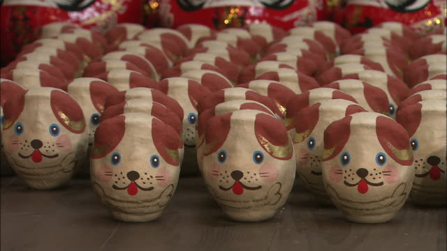 tilt down from stack of daruma dolls to rows of dog of oriental zodiac dolls - bambola daruma video stock e b–roll