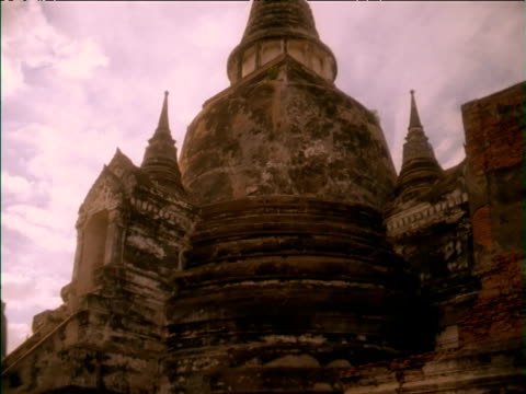 Tilt down from stone temple and zoom in to woman carrying hanging baskets of flowers from shoulder pole, Thailand