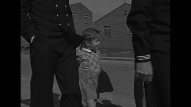 Tilt down from street sign to mothers servicemen walking with children on street in front of row houses / police officer sailor Naval officer walk...