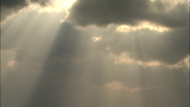 tilt down from sun beams shining through cloud to light reflecting on sea of japan - tilt down stock videos & royalty-free footage