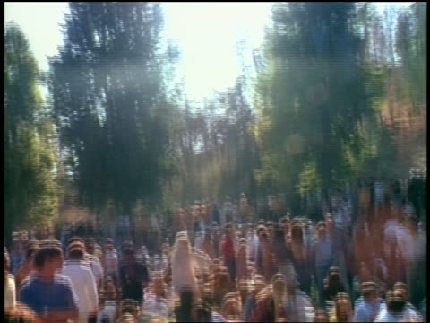 tilt down from sun to crowd of hippies sitting on ground at be-in - 1968 stock videos & royalty-free footage