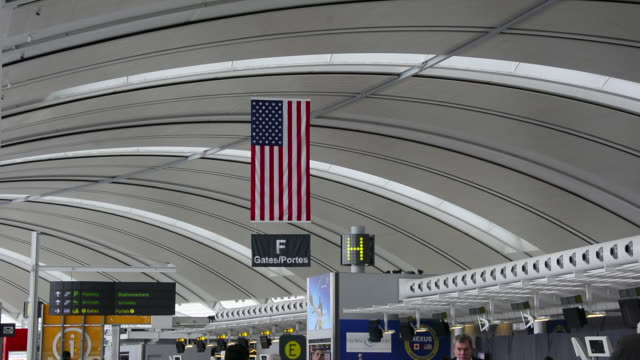 tilt down from the american flag to the departure area. the landmark is the primary international airport serving toronto and the surrounding areas.... - international landmark video stock e b–roll