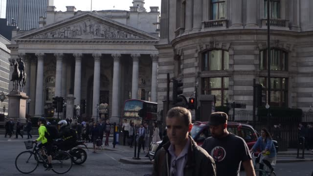 Tilt down from the Bank of England left and the Royal Exchange to morning commuters walking along street during the morning rush hour in the City of...