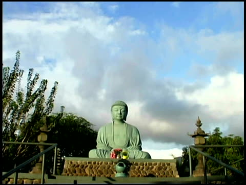 tilt down from the sky to a wide shot looking up stairs to a buddha statue. - weibliche figur stock-videos und b-roll-filmmaterial