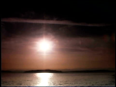 tilt down from the sky to the sun setting over the puget sound. - puget sound stock videos & royalty-free footage