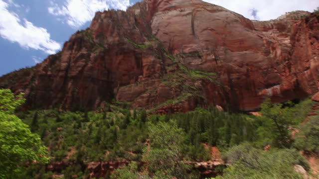 tilt down from top of rocky mountains and blue skies to mother and son standing and looking out during a hike in zion national park - zion national park stock videos & royalty-free footage
