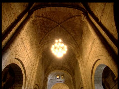 stockvideo's en b-roll-footage met tilt down from vaulted ceiling of church including arches and light in centre to aisle with altar at end and pews to sides; santillana spain - altaar