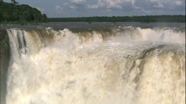 tilt down from water pouring over devil's throat section of iguazu falls, border of brazil and argentina - devil's throat stock videos and b-roll footage