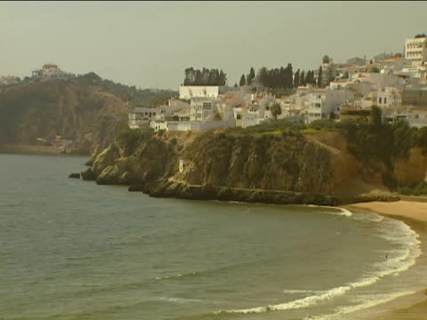 Tilt down from whitewashed apartments on cliffs to sea and people walking along sandy beach Fisherman's Beach