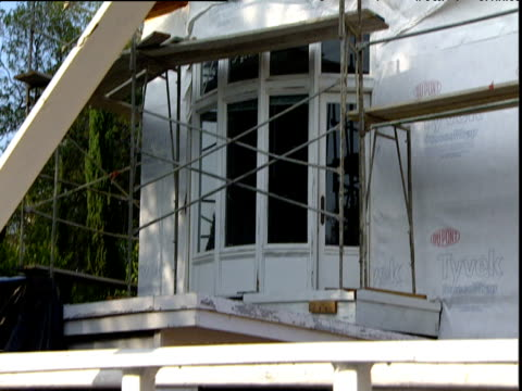 tilt down from windows of house with scaffolding to - erektion stock-videos und b-roll-filmmaterial