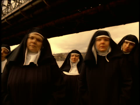 vídeos de stock, filmes e b-roll de tilt down from yellow sky to ms group of nuns standing under bridge bobbing heads to beat of music / prague - nun