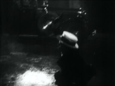 B/W 1934 tilt down gangster in hat with gun falling to the ground in street after being shot