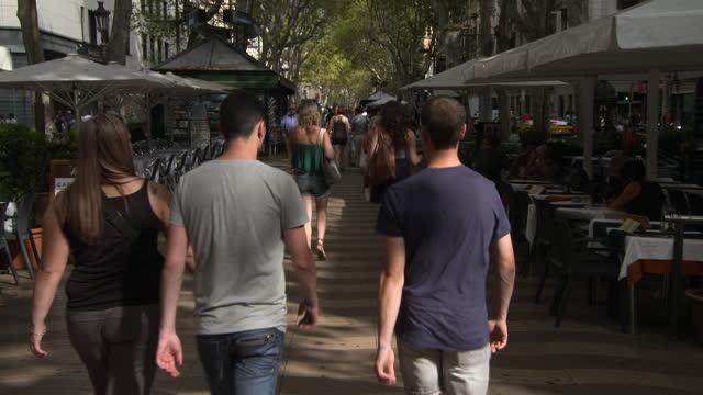 tilt down: green branches form canopy above long pedestrian street with groups of tourists and outdoor dining - barcelona, spain - tropiskt träd bildbanksvideor och videomaterial från bakom kulisserna
