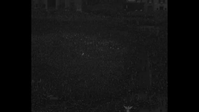 stockvideo's en b-roll-footage met tilt down huge group of fascist soldiers jog by in formation carrying flags / aerial: crowd of thousands / italian military marches by carrying large... - 1930