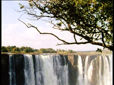 tilt down huge waterfall with slight rainbow - victoria falls stock videos and b-roll footage