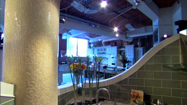 tilt down in a kitchen showroom to a high angle view of a kitchen sink and granite counter. - showroom stock videos and b-roll footage