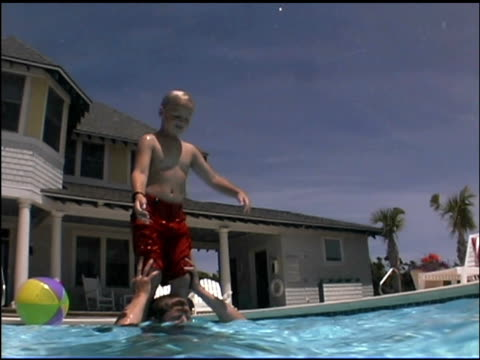 tilt down in the swimming pool of boy jumping from his father's shoulders. the viewer follows the action from above to under the water. - see other clips from this shoot 1135 stock videos & royalty-free footage