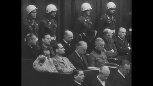 tilt down international military tribunal panel of judges seated at long desk during nuremberg trials at the nuremberg palace of justice with people... - processi di norimberga video stock e b–roll