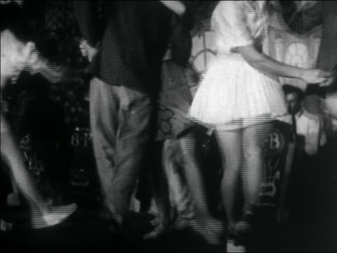B/W 1938 tilt down legs of teens swing dancing + kicking / big band in background / documentary