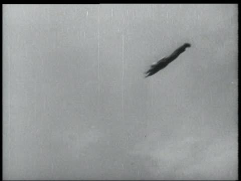 b/w 1952 tilt down long shot man in flying suit descending in air - 1952 stock videos & royalty-free footage