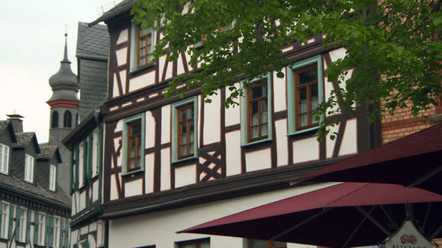 tilt down: lush tree foliage before stunning timbered medieval three story building under overcast sky - frankfurt, germany - hesse germany stock videos & royalty-free footage