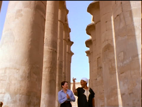 tilt down male Egyptian guide walking with tourist woman past large columns / Temple of Luxor / Egypt