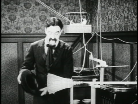 vídeos de stock, filmes e b-roll de b/w 1923 tilt down man (snub pollard) attaching broom to record player + brushing off hat + shoes / short - 1923