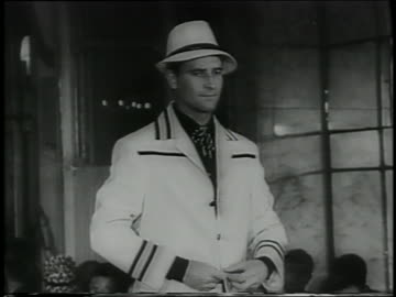 tilt down man in hat + trimmed white suit on runway in italian fashion show - sfilata di moda video stock e b–roll
