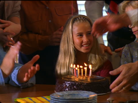 tilt down man putting birthday cake in front of girl / she blows out candles, family claps