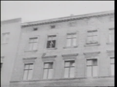 vídeos de stock e filmes b-roll de b/w 1961 tilt down man throwing belongings from building window then jumping into net on ground / berlin - 1961