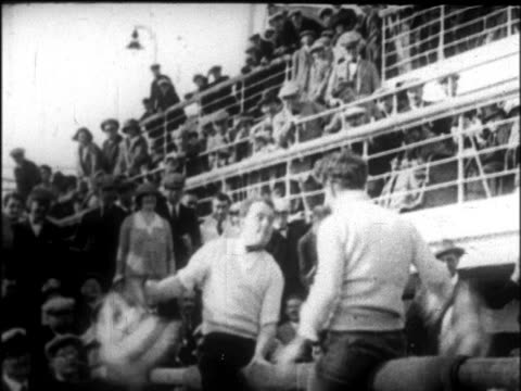 b/w 1926 tilt down men on sawhorse having pillow fight on deck of cruise ship / newsreel - 1926 stock videos & royalty-free footage