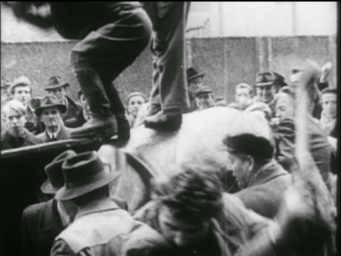 vídeos de stock e filmes b-roll de tilt down men with sledgehammers + saws attack russian tank / crowd in background / hungarian uprising - 1956