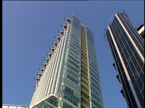 tilt down modern glass building against blue sky - fensterfront stock-videos und b-roll-filmmaterial