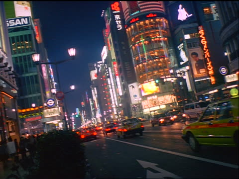 vídeos de stock e filmes b-roll de tilt down pan neon lights + traffic on busy city street in ginza district of tokyo at night / japan - 1999