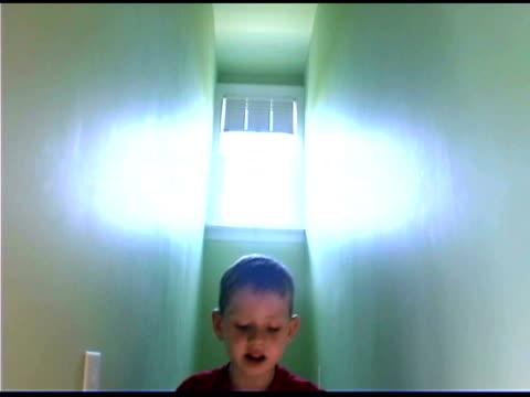 tilt down of boy reading in hallway - 胡坐点の映像素材/bロール