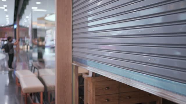 vídeos de stock, filmes e b-roll de incline-se para baixo de loja fechada com porta de metal em shopping center - fechar